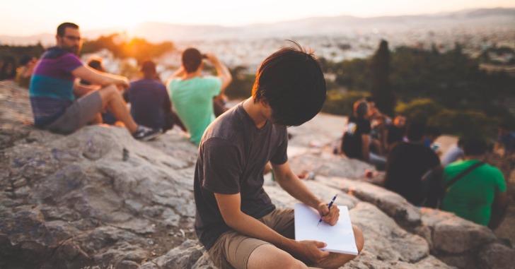 岩の上に座って絵を描く少年