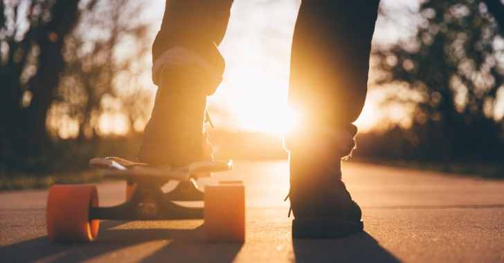 夕日を浴びるスケートボードと足