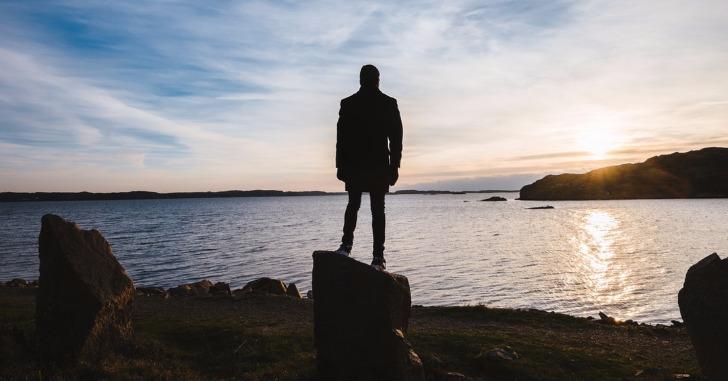 海に向かって立つ男性の後ろ姿