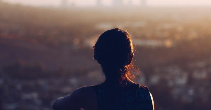 夕焼けの中で座り込み街並みを眺める女性の後ろ姿