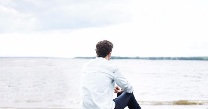 座り込んで海を眺める男性の後ろ姿