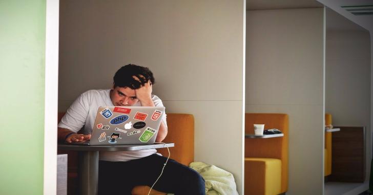 ノートパソコンの前に座り頭を抱えている男性