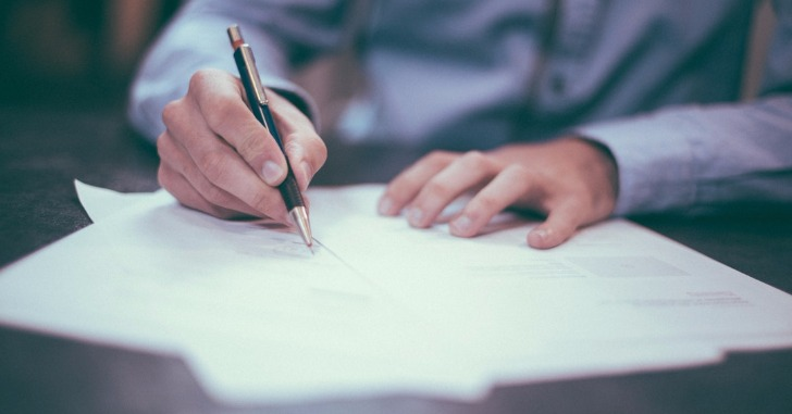 ペンで書類に何かを書いている人