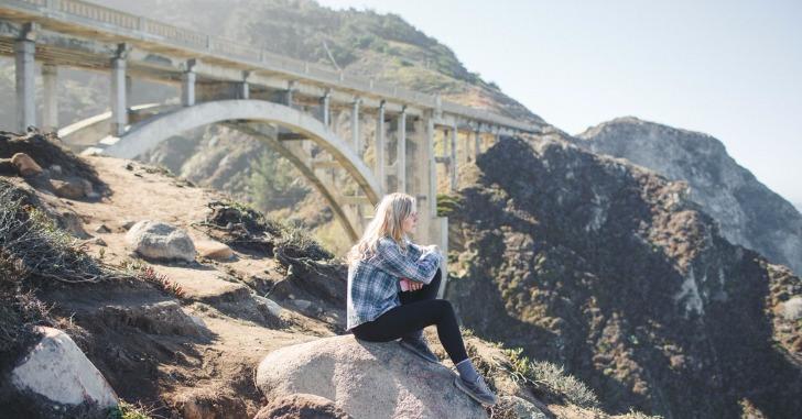 橋を背景に岩の上に座り遠くを眺める女性