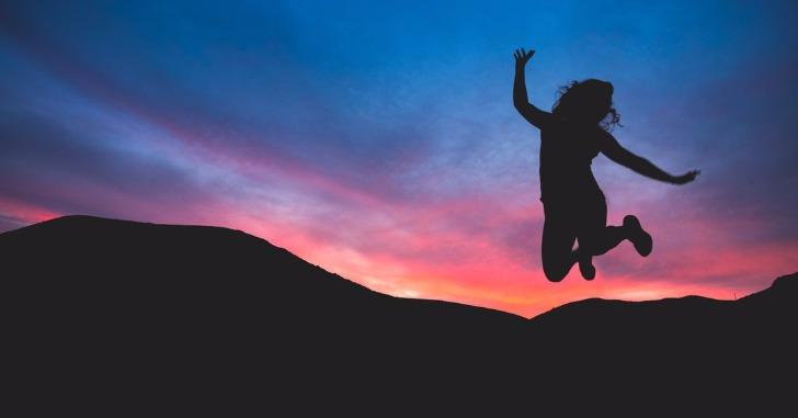夕暮れの中でジャンプする女性