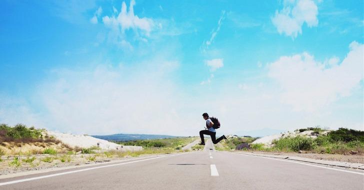 青空の下道路上でジャンプする男性