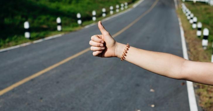右手親指を立ててヒッチハイクする人の右腕