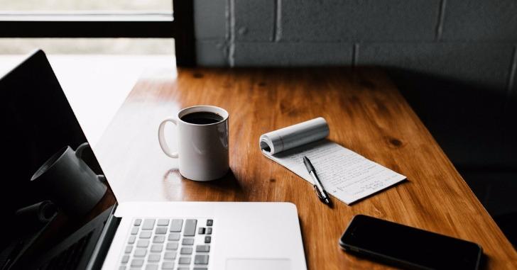 ノートパソコンとコーヒーとペンとメモ帳とスマホ