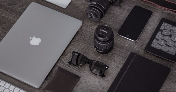 机の上に並べられたノートパソコンとメガネとカメラとその他