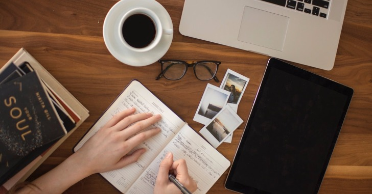 ノートパソコンとコーヒーとメガネと写真とメモ帳に何かを書く手